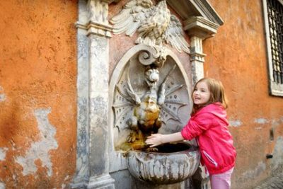 Adorable little girl playing with drinking water fountain in Rome,  Italy